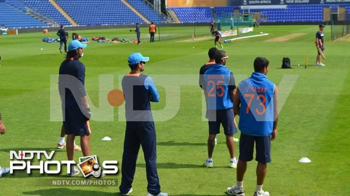 Ishant Sharma, Shikhar Dhawan and Umesh Yadav watch the proceedings from a distance as their mates take turns at practice at the hands of the coach.