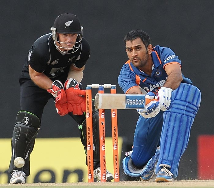 Indian cricket captain Mahendra Singh Dhoni is watched by New Zealand wicketkeeper Gareth Hopkins as he plays a shot during the sixth ODI of the Micromax tri-series between India and New Zealand at the Rangiri Dambulla International stadium in Dambulla. (AFP Photo)