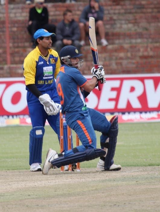 Indian batsman Virat Kohli plays a shot while Sri Lanka captain and wicketkeeper Tillekeratne Dilshan looks on during a match against Sri Lanka at Queens Sports Club in Bulawayo. (AP Photo)