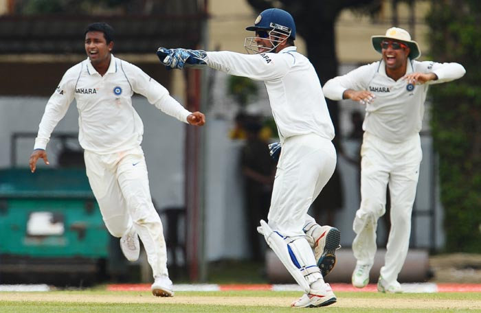 Indian cricket captain Mahendra Singh Dhoni celebrates with teammates VVS Laxman and Pragyan Ojha the dismissal of Tillakaratne Dilshan during the first day of the third Test match between Sri Lanka and India at the P. Sara Oval International Cricket Stadium in Colombo. (AFP Photo)