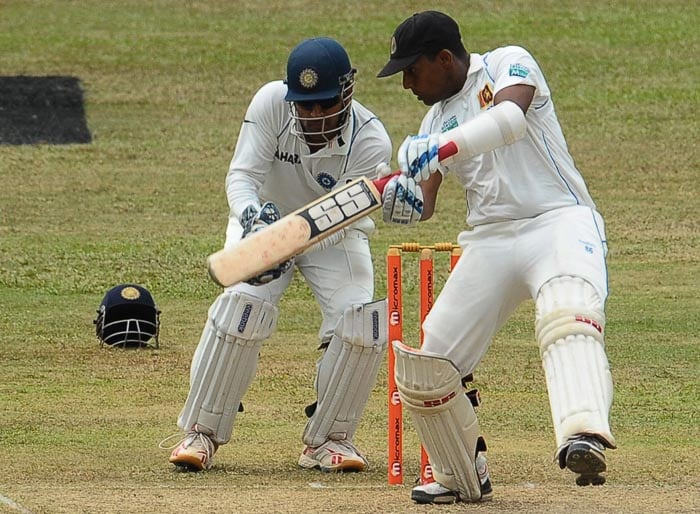 Sri Lankan cricketer Thilan Samaraweera plays a stroke while watched by Indian captain and wicketkeeper Mahendra Singh Dhoni during the first day of the third Test match between Sri Lanka and India at the P. Sara Oval International Cricket Stadium in Colombo. (AFP Photo)