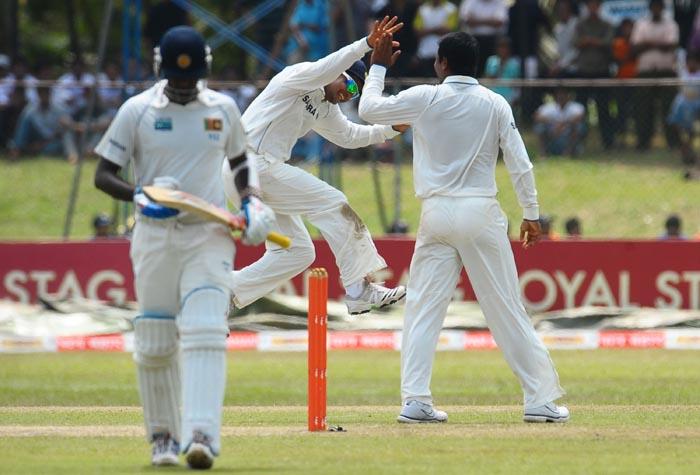 Indian cricketer Pragyan Ojha celebrates with teammate Surehs Raina after the dismissal of Sri Lankan batsman Anjelo Mathews at The P. Sara Oval International Cricket Stadium in Colombo. (AFP Photo)