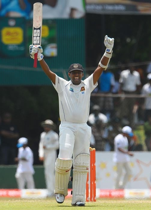Sri Lankan cricketer Thilan Samaraweera raises his bat in celebration after scoring a century during the second day of the third Test match between Sri Lanka and India at The P. Sara Oval International Cricket Stadium in Colombo. (AFP Photo)