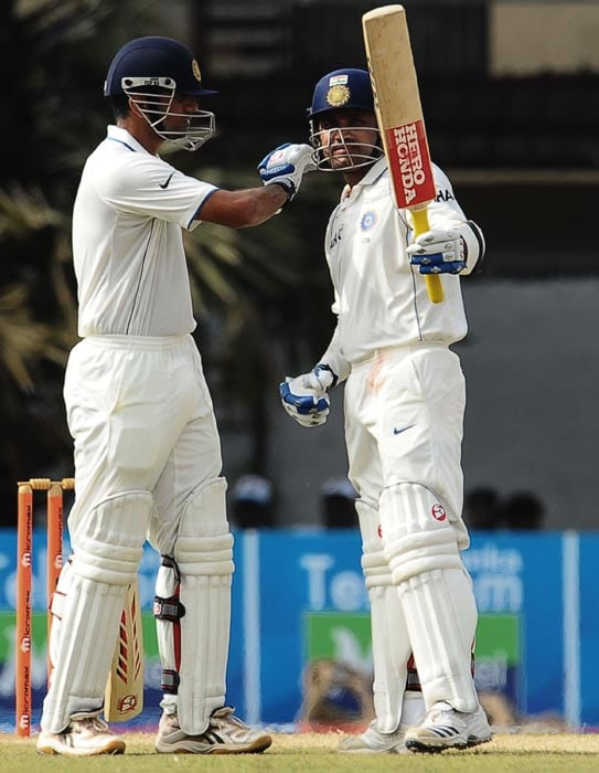 Indian cricketer Virender Sehwag is watched by his teammate Rahul Dravid as he raises his bat to the crowd after scoring a half-century during the second day of the third Test match between Sri Lanka and India at The P. Sara Oval International Cricket Stadium in Colombo. (AFP Photo)
