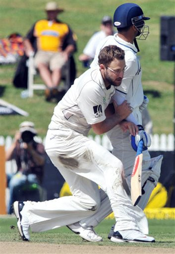 Daniel Vettori runs into Rahul Dravid on the second day of the first Test in Hamilton, New Zealand. (AP Photo)
