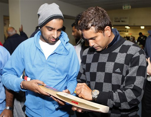 Sachin Tendulkar, right, signs his autograph on his arrival at Christchurch airport on Friday, February 20, 2009. India will play three Test matches, five one-day internationals and two twenty20 matches during the cricket tour of New Zealand. (AP Photo)