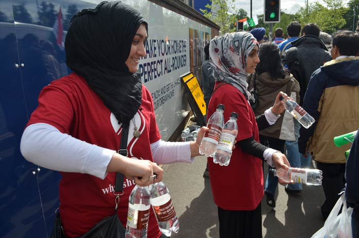 Volunteers hand out water bottles so that they can quench their thirst as they give full force to their voices in the stadium.