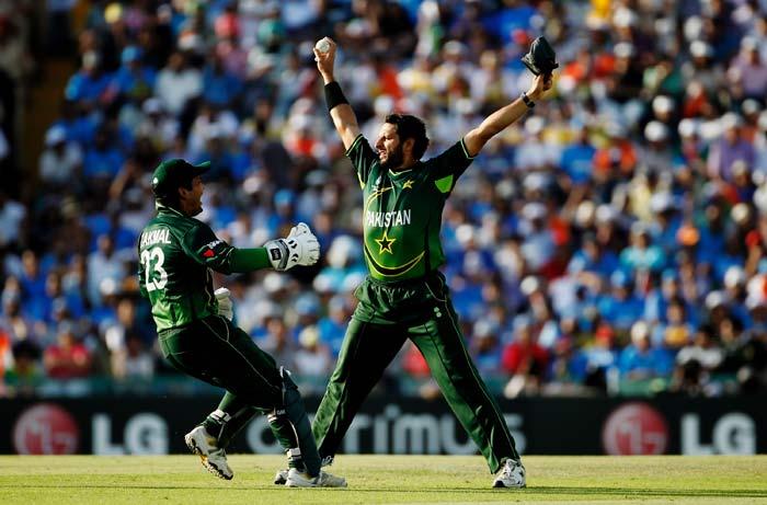 Captain Shahid Afridi celebrates with team mate Kamran Akmal after taking the catch to dismiss Sachin Tendulkar. (AFP Photo)