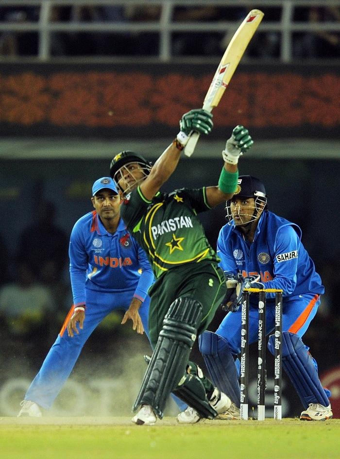 Pakistan batsman Umar Akmal hits a six as Indian captain Mahendra singh Dhoni and Virender Sehwag. (AFP Photo)