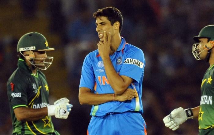 Indian bowler Ashish Nehra reacts after being hit for a boundary by Pakistan batsman Kamran Akmal. (AFP Photo)