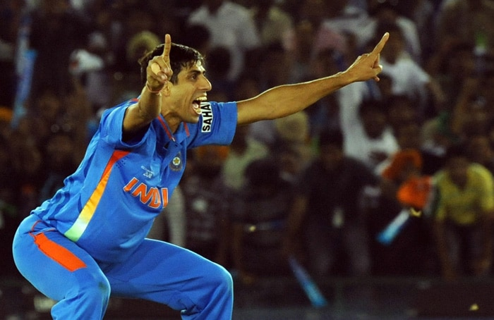 Indian cricketer Ashish Nehra reacts after taking the wicket of unseen Pakistan batsman Umar Gul. (AFP Photo)