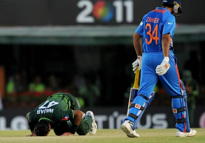 Pakistani fast bowler Wahab Riaz bows down on the pitch after taking his fifth wicket as India's Zaheer Khan. (AFP Photo)