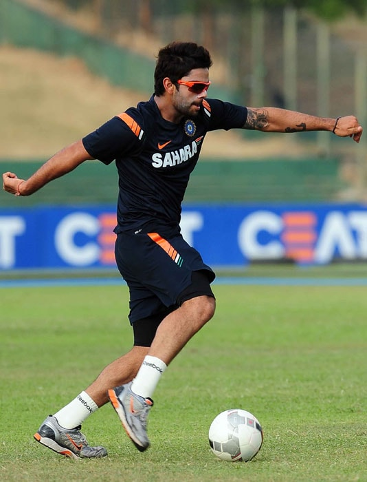 Indian cricketer Virat Kohli plays football during a training session in Dambulla. (AFP PHOTO)
