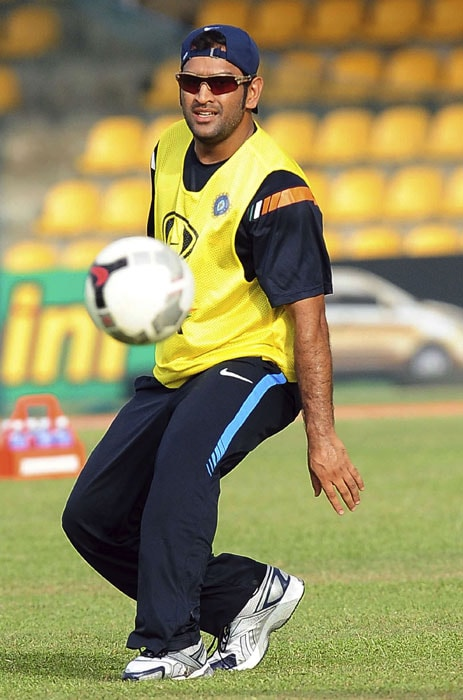 Indian cricket team captain Mahendra Singh Dhoni watches the ball while playing soccer during a practice session. (AFP PHOTO)