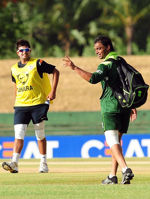 Pakistan cricketer Shoaib Akhtar gestures as Indian cricketer Suresh Raina looks on. (AFP PHOTO)
