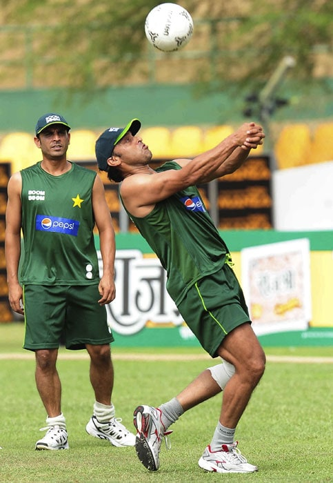 Pakistan cricketer Shoaib Akhtar balances a ball as teammate Imran Farhat looks on. (AFP PHOTO)