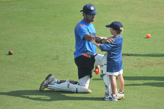 Yuvraj Singh speaks with Indian coach Gary Kirsten's son, Joshua during a training session ahead of the final Test against Sri Lanka in Mumbai. (AFP Photo)