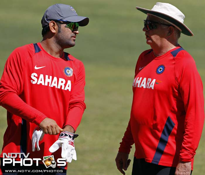 Indian captain Mahendra Singh Dhoni (L) talks with coach Duncan Fletcher while getting ready for a practice session in Kingston, Jamaica. (AP Photo)