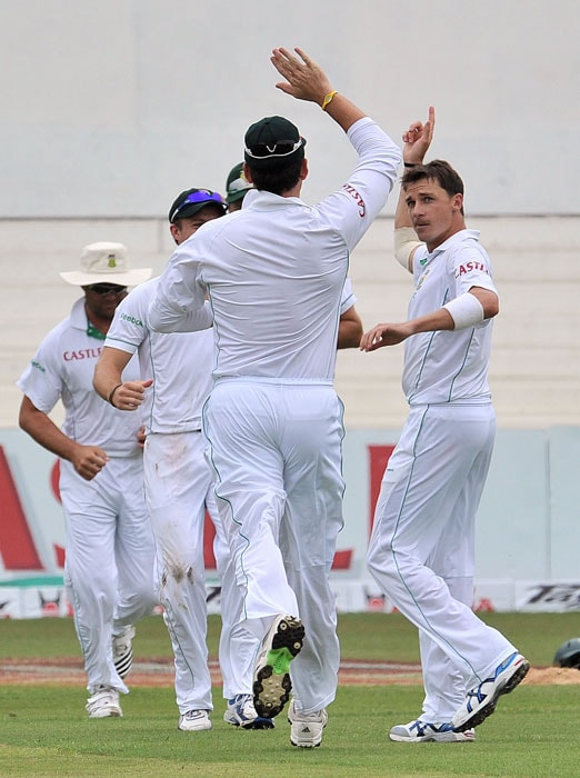 Dale Steyn is congratulated by teammates for getting out Virender Sehwag for 25 runs on the first day of the second Test at Kingsmead Stadium in Durban. (AFP Photo)