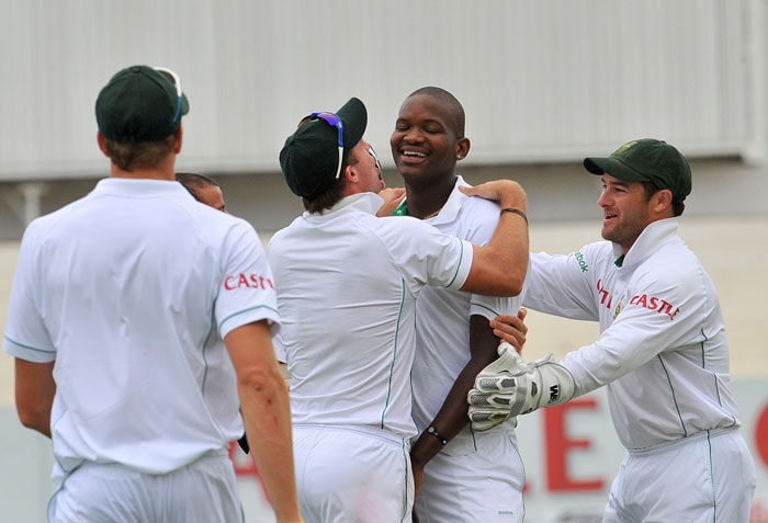 Lonwabo Tsotsobe is congratulated by teammates for dismissing Sachin Tendulkar for 13 runs on the first day of the second Test at Kingsmead Stadium in Durban. (AFP Photo)