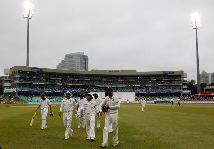 Players leave the field as as play is delayed by bad light on the third day of the second test match at the Kingsmead stadium in Durban. (AP Photo)