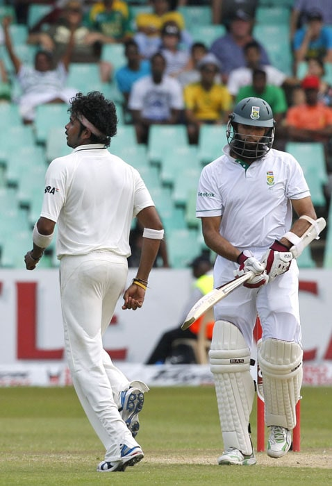 South Africa's batsman Hashim Amla looks on as India's bowler Shanthakumaran Sreesanth, celebrates his wicket on the third day of the second test match at the Kingsmead stadium in Durban. (AP Photo)