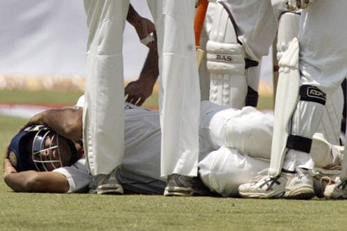 Sourav Ganguly lie on the ground as teammates attend to him, while a ball off South Africa's Hashim Amla landed on his headgear during the first day of third cricket Test match of the Future Cup series in Kanpur on Friday, April 11, 2008.