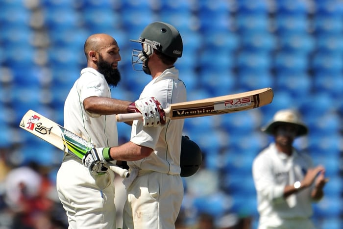 Hashim Amla is congratulated by his teammate AB de Villiers after Amla hit a double century on the second day of the first cricket Test match between India and South Africa in Nagpur. (AFP Photo)