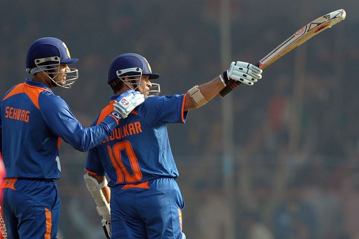 Virender Sehwag congratulates teammate Sachin Tendulkar on scoring a half-century during the first ODI match in Rajkot. (AFP Photo)