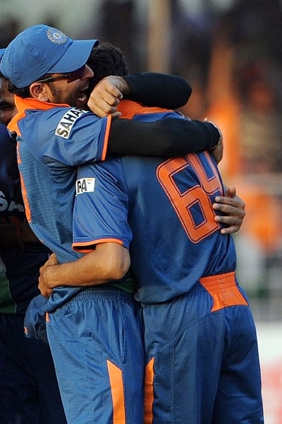 Yuvraj Singh hugs Ashish Nehra after winning the first ODI between India and Sri Lanka in Rajkot. India overcame a brilliant century by Tillakaratne Dilshan to defeat Sri Lanka by three runs in a dramatic start to the five-match one-day series. Dilshan made 160 off 124 balls as the tourists made a spirited effort to surpass India's highest one-day total of 414-7, before falling agonisingly short in a high-scoring thriller. (AFP Photo)