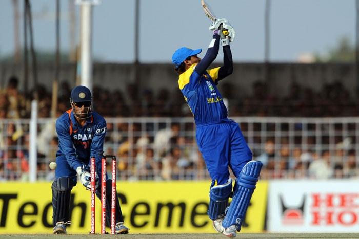 MS Dhoni reacts as Sri Lankan batsman Tillakaratne Dilshan gets bowled by Harbhajan Singh during the first ODI between India and Sri Lanka in Rajkot. (AFP Photo)