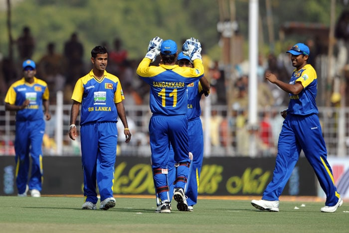 Sri Lankan cricketers celebrate the wicket of Suresh Raina during the first ODI between India and Sri Lanka in Rajkot. (AFP Photo)