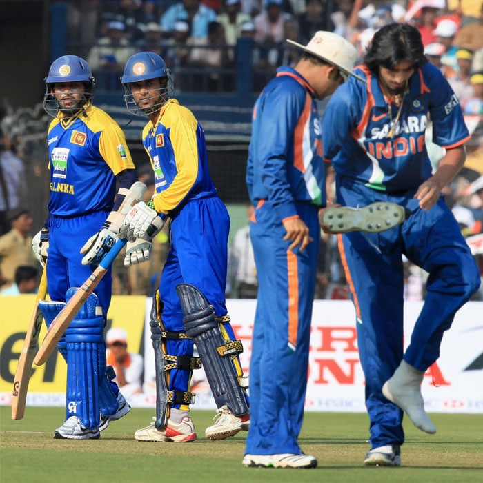 Ishant Sharma having problem with his shoes as captain Virendra Sehwag helps him during the 3rd ODI between India and Sri Lanka at Barabati Stadium in Cuttack. (PTI Photo)