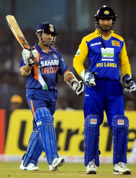 Sachin Tendulkar raises his bat on completing his half-century as Sri Lankan captain Kumar Sangakarra looks on during the 3rd ODI at Barabati Stadium in Cuttack. (PTI Photo)