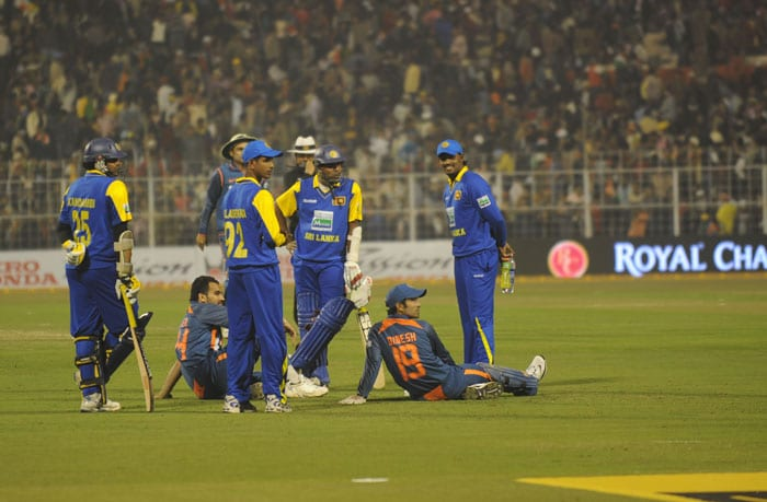 Indian and Sri Lankan cricketers wait as the flood lights go off during the middle of the fourth ODI between India and Sri Lanka at Eden Gardens Stadium in Kolkata. (AFP Photo)