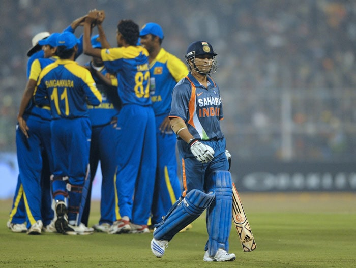 Sachin Tendulkar walks off the pitch after his dismissal as Sri Lankan fielders celebrate during the fourth ODI between India and Sri Lanka at Eden Gardens Stadium in Kolkata. (AFP Photo)