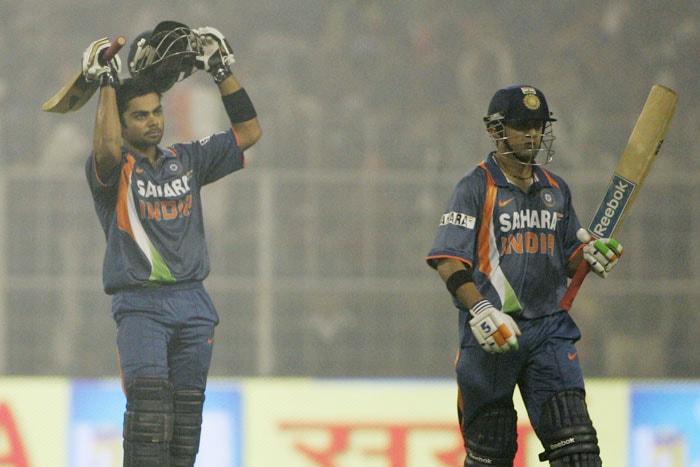 Virat Kohli acknowledges the crowd after scoring a century as Gautam Gambhir walks on during the fourth ODI between India and Sri Lanka in Kolkata. (AP Photo)