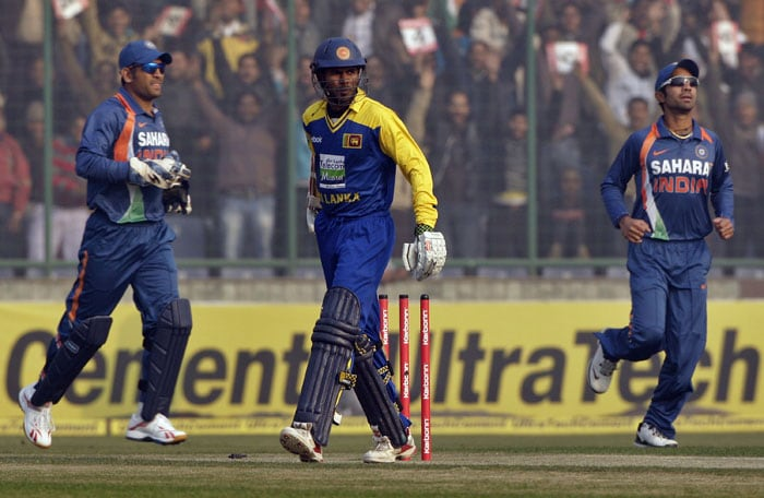 Upul Tharanga walks back to the pavilion after being bowled out as Mahendra Singh Dhoni and teammate Dinesh Karthik run to celebrate during the fifth and final ODI between India and Sri Lanka in New Delhi. (AP Photo)