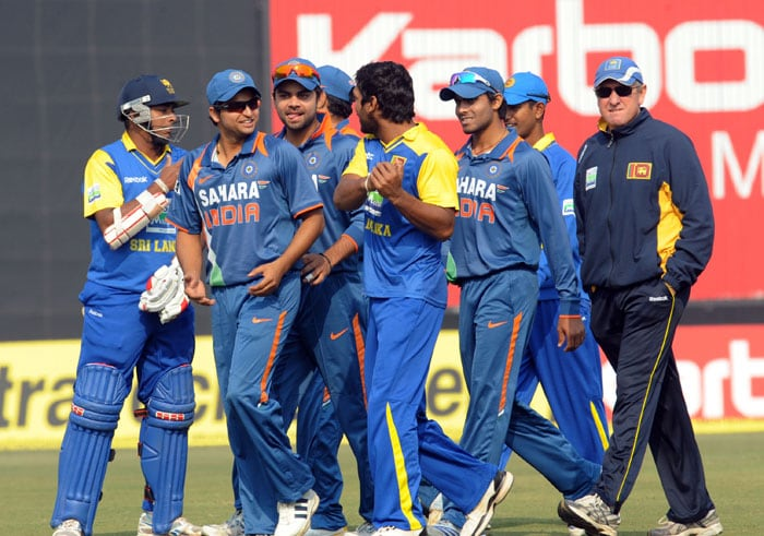 Kumar Sangakkara gestures as he speaks with Suresh Raina as they walk with teammates off the pitch during the fifth and final ODI between India and Sri Lanka at the Feroz Shah Kotla in New Delhi. (AFP Photo)