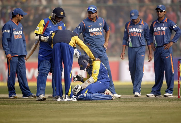 Tillakaratne Dilshan reacts in pain as he is attended by a member of his team support staff as teammate Sanath Jayasuriya and Indian cricketers look on after he was hit by a ball from India's Ashish Nehra during the fifth and final ODI between India and Sri Lanka in New Delhi. (AP Photo)
