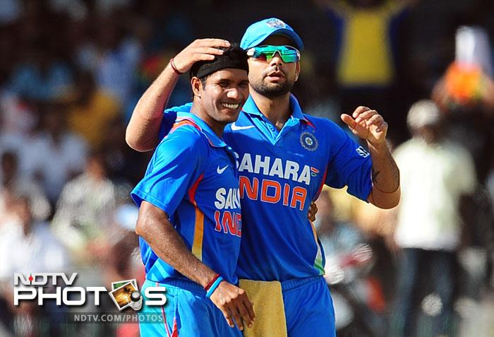 Ashok Dinda, seen here with Virat Kohli, got India the first breakthrough when he dismissed Dilshan. India got regular Lankan wickets after that to keep the scoring in check.