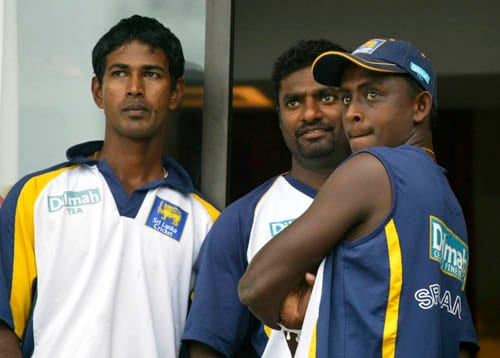 Sri Lankan bowlers from left, Nuwan Kulasekara, Muttiah Muralitharan and Ajantha Mendis look on, as ground staff, unseen, cover the ground in Colombo.