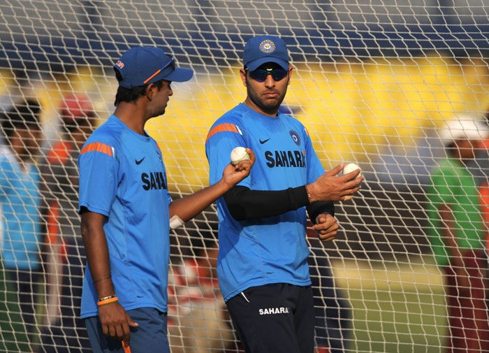 Yuvraj Singh and teammate Pragyan Ojha chat during a practice session at the Barabati Stadium in Cuttack ahead of the third ODI against Sri Lanka. (AFP Photo)