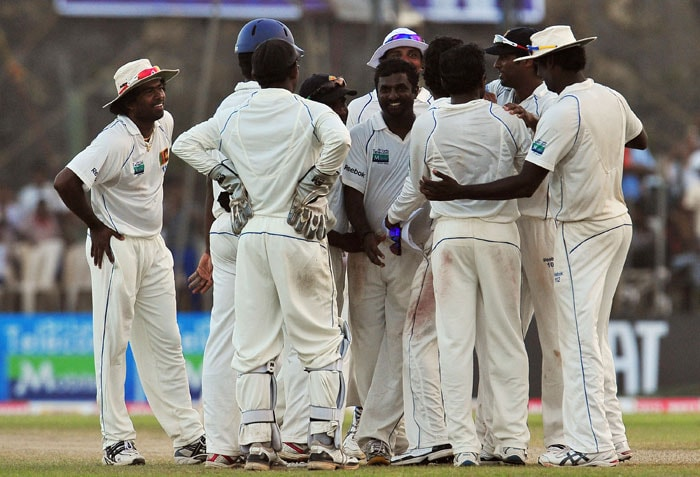 Sri Lankan cricketer Muttiah Muralitharan (Center) is congratulated by his teammates after dismissing unseen Indian cricketer Yuvraj Singh during the fourth day of the first Test match between Sri Lanka and India at The Galle International Cricket Stadium in Galle on July 21, 2010.<br><br> Sri Lanka enforced the follow-on with a lead of 244 runs over India on the fourth day of the first Test. India were all out for 276 in their first innings in reply to Sri Lanka's 520-8 declared. World bowling record holder Muttiah Muralitharan, who retires after this match, finished with 5-63 to take his career tally to 798 Test wickets. (AFP Photo)