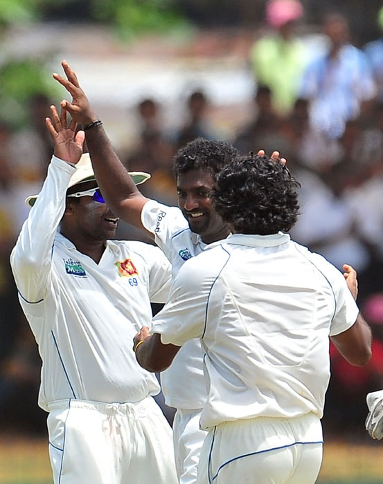 Sri Lankan cricketer Muttiah Muralitharan (C) is congratulated by teammates Mahela Jayawardene (L) and Lasith Malinga (R) after dismissing unseen Indian captain Mahendra Singh Dhoni during the fourth day of the first Test match between Sri Lanka and India at The Galle International Cricket Stadium. (AFP Photo)