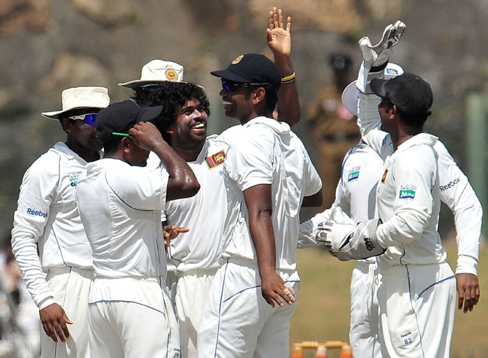 Sri Lankan cricketer Lasith Malinga (C) celebrates with teammates after the dismissal of unseen Indian batsman VVS Laxman during the fourth day of the first Test match between Sri Lanka and India at The Galle International Cricket Stadium. (AFP Photo)