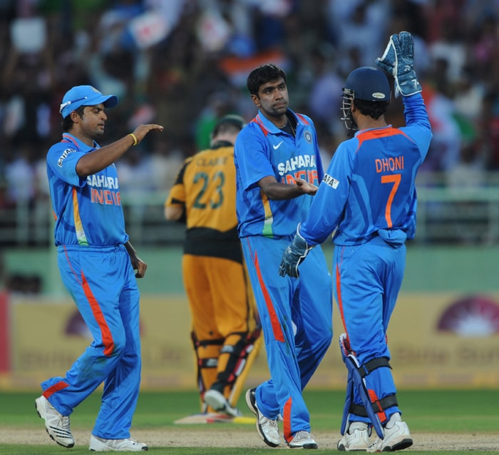 India's Mahendra Singh Dhoni (R) greets teammate Ravichandran Ashwin (C) for dismissing unseen Australian cricketer Michael Hussey during the second ODI between India and Australia at The Y.S. Rajasekhara Reddy ACA-VDCA Cricket Stadium in Visakhapatnam. (AFP Photo)