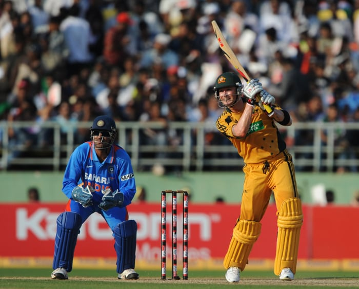 Australian cricketer Michael Clarke (R) is watched by Indian wicketkeeper Mahendra Singh Dhoni as he plays a shot during the second ODI between India and Australia at The Y.S. Rajasekhara Reddy ACA-VDCA Cricket Stadium in Visakhapatnam. (AFP Photo)