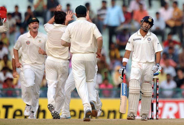 Indian cricketer Gautam Gambhir reacts as Australian cricketers celebrate the taking of his wicket during the fourth day of the first Test between India and Australia in Mohali. (AFP Photo)