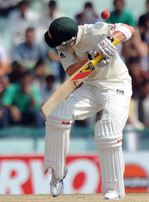 Australian cricketer Michael Clarke tries to duck a ball as it touches his gloves to go as a catch to Indian wicketkeeper Mahendra Singh Dhoni during the fourth day of the first Test between India and Australia in Mohali. (AFP Photo)